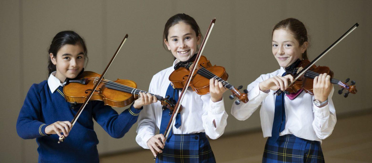 three girls holding violins