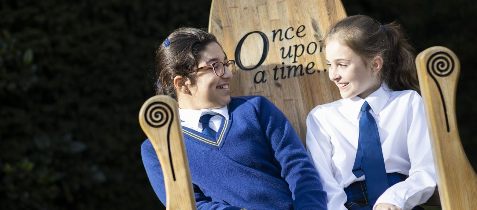 """two school girls sitting on a wooden chair with """"Once Upon a Time"""" engraving"""