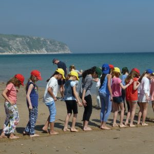children forming a line on the beach