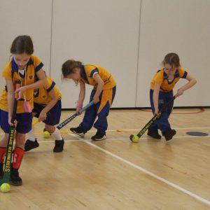 children playing hockey indoors